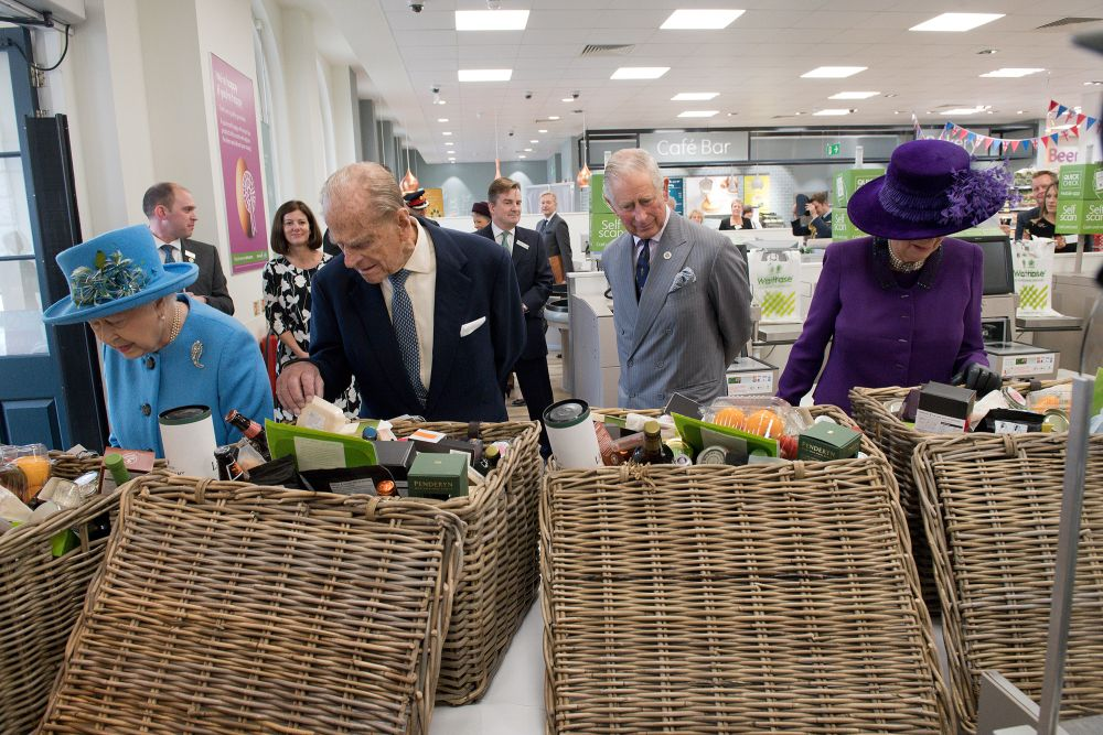 POUNDBURY, ENGLAND - OCTOBER 27: (L-R) Britain's Queen Elizabeth II, Prince Philip, Duke of Edinburgh, Prince Charles, Prince of Wales and Camilla, Duchess of Cornwall look at food hampers during a visit to a Waitrose supermarket in the town on October 27, 2016 in Poundbury, England.  The Queen and The Duke of Edinburgh, accompanied by The Prince of Wales and The Duchess of Cornwall, visited Poundbury. Poundbury is an experimental new town on the outskirts of Dorchester in southwest England designed by Leon Krier with traditional urban principles championed by The Prince of Wales and built on land owned by the Duchy of Cornwall.(Photo by Justin Tallis - WPA Pool/Getty Images)